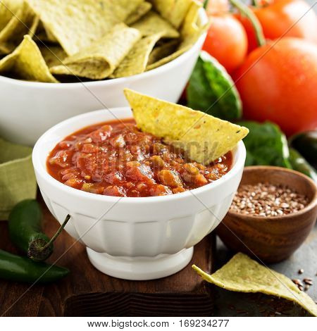 Red tomato spicy salsa with green torltilla corn chips