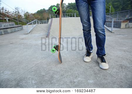 closeup of skateboarder with skateboard on skatepark