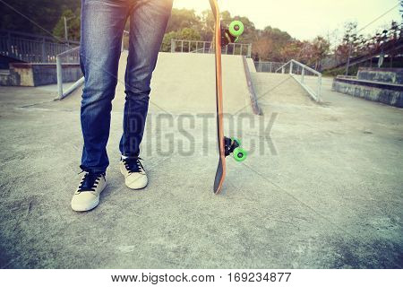 closeup of skateboarder with skateboard on skatepark