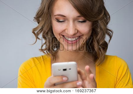 young woman wearing yellow shirt and jeans shorts  talk to phone and make faces over grey background