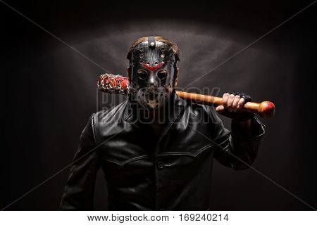 Psycho killer in hockey mask on black background.