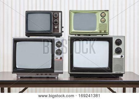 Four vintage televisions stacked on table.