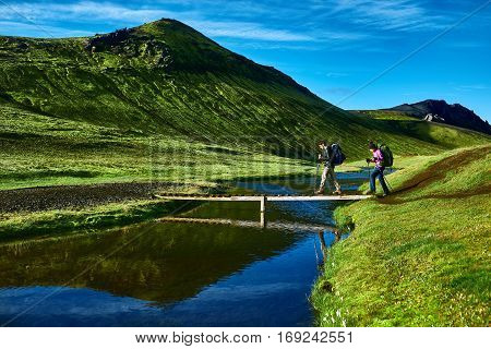 Travel to Iceland. Beautiful Icelandic landscape with hikers and bridge over creek, mountains, sky and clouds. Trekking in national park Landmannalaugar