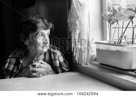 Elderly woman looks wistfully out the window. Black-and-white photo.