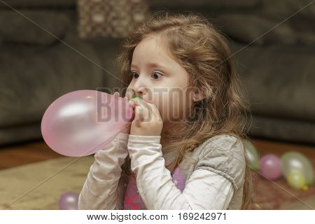 girls eyes bugging out as she tries to blow up a balloon