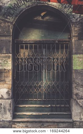 vintage sliding barred door in the dark tone for interior or exterior brick wall building decoration texture background