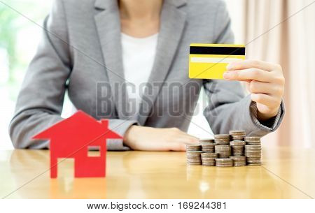 Real estate investment by credit card. House and coins on table.