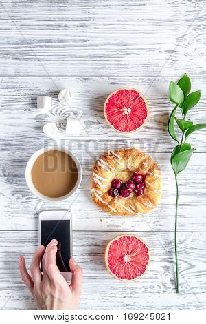 Breakfast concept with flowers on wooden background top view.