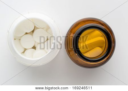top view of two bottles of different pills. On white background