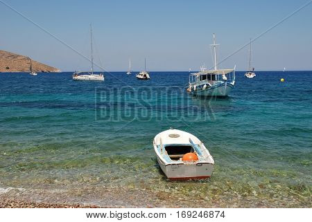 TILOS, GREECE - JULY 19, 2016: Small boats moored off Livadia beach on the Greek island of Tilos. The 14.5km long Dodecanese island has a population of around 780 people.