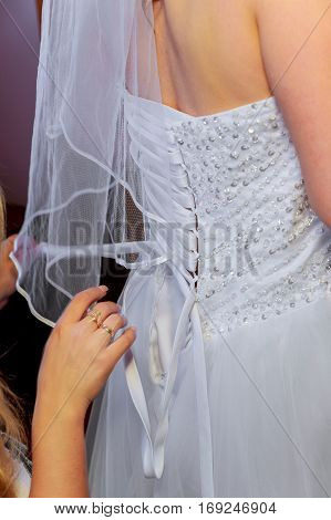Morning bride. Bridesmaid helping the bride lacing up her dress