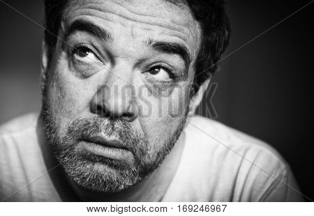 Low-key black and white monochrome portrait of a sad middle-aged man. Selective focus.