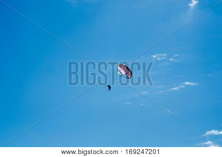 Bright parasailing couple against bright blue sky.