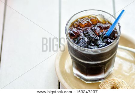 Glass with cold brewed coffee on white wooden background. Place for your text