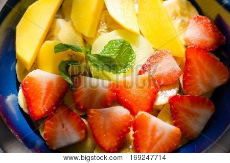 Clay bowl with fruit oatmeal. Strawberry mango and banana slices