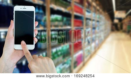Woman using smart phon while shopping in supermarket