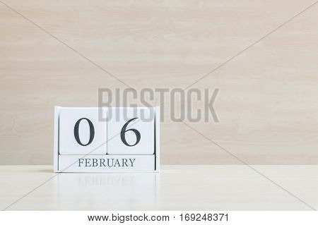 Closeup surface white wooden calendar with black 6 february word on blurred brown wood desk and wood wall textured background with copy space in selective focus at the calendar