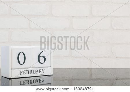 Closeup white wooden calendar with black 6 february word on black glass table and white brick wall textured background with copy space in selective focus at the calendar