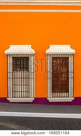 Two windows with bars on orange wall down the street