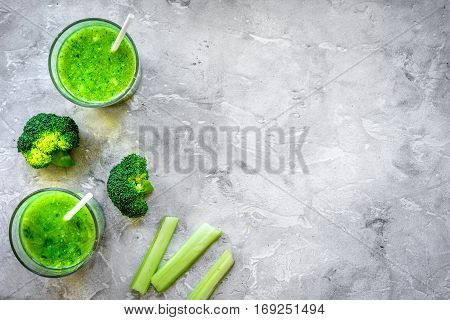 Green vegetable smoothie in glass at gray background top view.