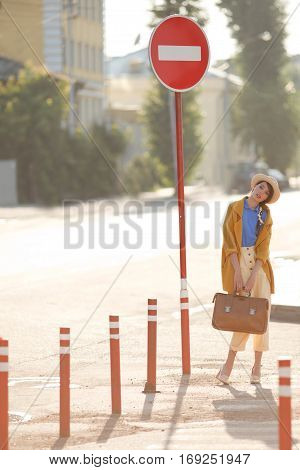 Young happy funny (vintage) dressed woman with retro suitcase stands on the street near red small columns and road sign. Picture ideal for illustating woman magazines.