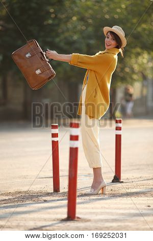 Young happy funny (vintage) dressed woman throws retro suitcase on the street near red small columns. Picture ideal for illustating woman magazines.