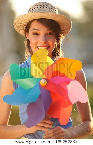 Young happy funny (vintage) dressed woman with colorful weather vane in her teeth. Picture ideal for illustating woman magazines.