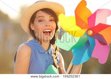 Young happy funny (vintage) dressed woman close-up with colorful weather vanelooking like flower Picture ideal for illustating woman magazines.