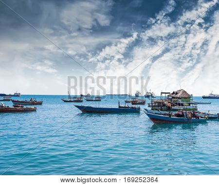 seascape with many anchored fishing boats near an african island