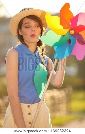 Young happy funny (vintage) dressed woman close-up making funny face and holding colorful weather vanelooking like flower Picture ideal for illustating woman magazines.