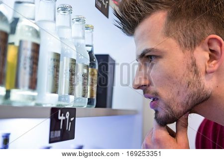 Close-up of man looking at beer bottles displayed on shelf in cafe