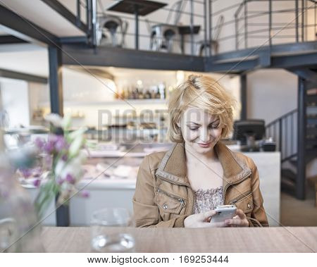 Happy young woman reading text message on cell phone in cafe