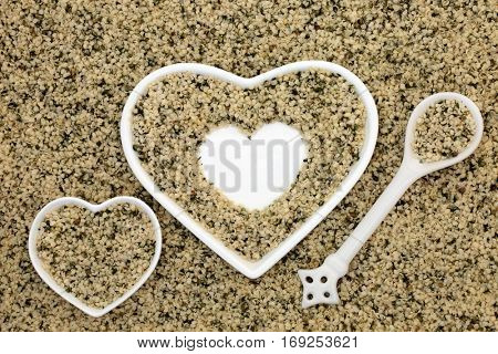 Hulled hemp seed health food in heart shaped dishes, spoon and loose forming a background.