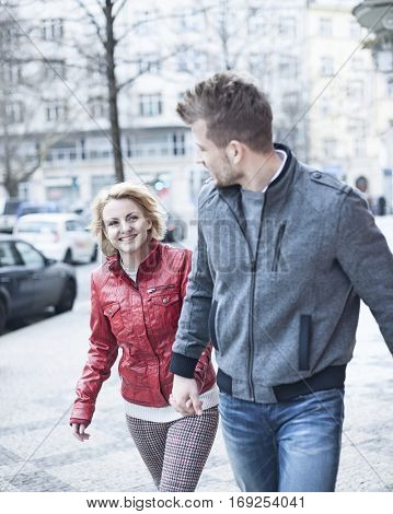 Happy young couple holding hands while walking on city street