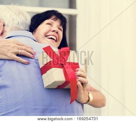 Wife hugging husband for the present