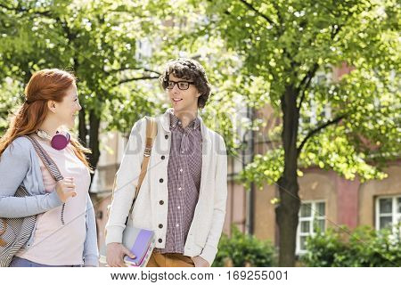 Young male and female college students talking while walking on street