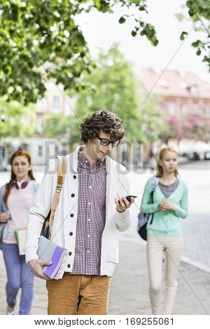 Young male student using cell phone with friends in background on street