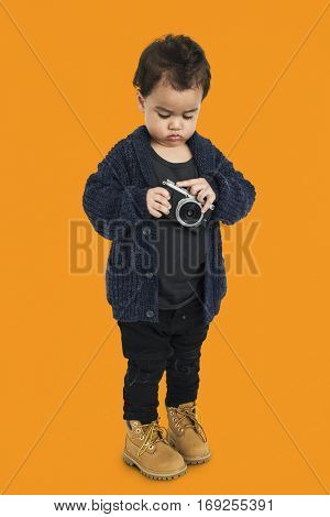 Curious Little Boy Holding Camera Concept