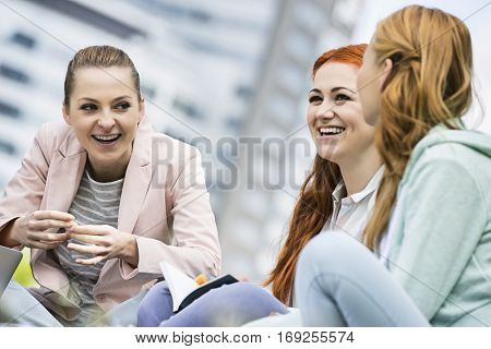 Happy young female college friends studying outdoors