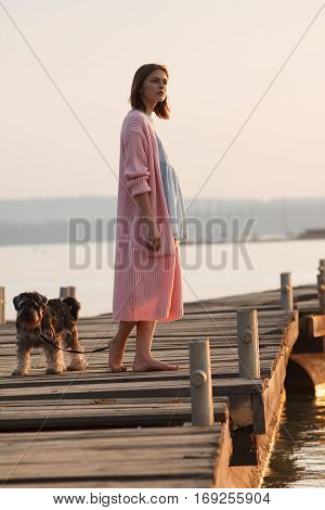 Young girl dressed in romantic style stands on old wooden pier with a dog on sunset. Professional style and make-up