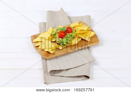corn tortilla chips with guacamole dip on wooden cutting board