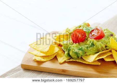 corn tortilla chips with guacamole dip on wooden cutting board - close up