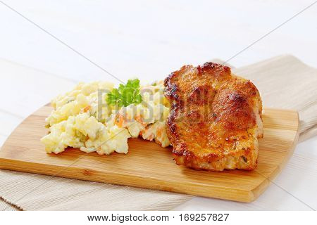 roasted chicken with potato salad on wooden cutting board - close up
