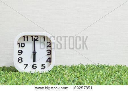 Closeup white clock for decorate in 6 o'clock on green artificial grass floor and cream wallpaper textured background with copy space