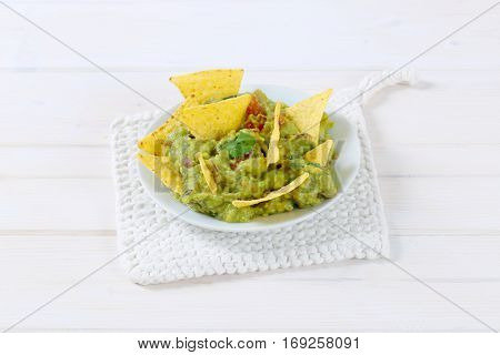 plate of guacamole with corn tortilla chips on white table mat