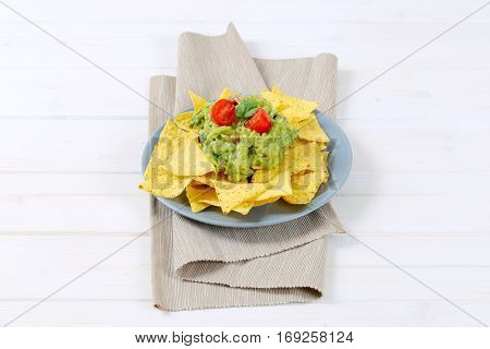plate of corn tortilla chips with guacamole dip on beige place mat