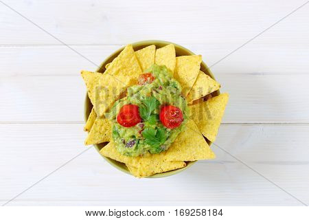 bowl of corn tortilla chips with guacamole dip on white background