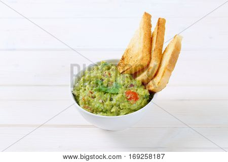 bowl of guacamole with toast bread on white background
