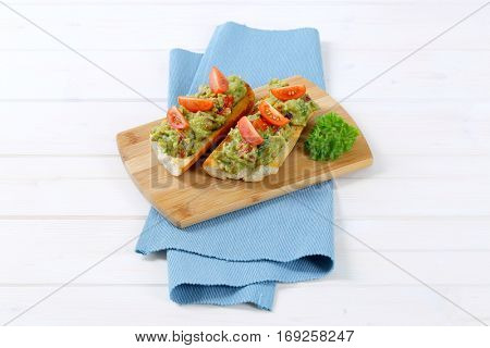 fresh baguettes with guacamole and tomatoes on wooden cutting board