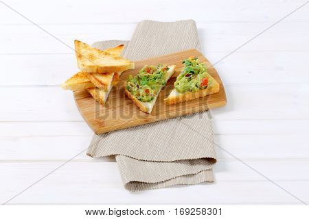toast bread with guacamole on wooden cutting board